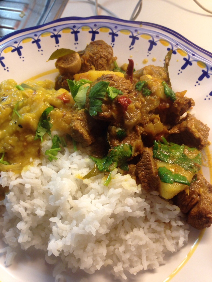 Lamb and potato curry served with basmati rice and red lentil dhal