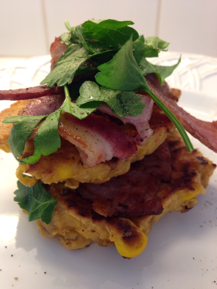 Spicy sweet corn fritters served with bacon, rocket and parsley