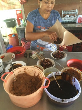 Making the satay sauce with crushed peanuts and kecap manis